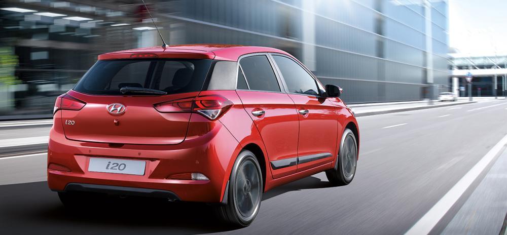 Varian Hyundai i20 berwarna merha dilihat dari sisi belakang sedang berjalan di jalan Indonesia
