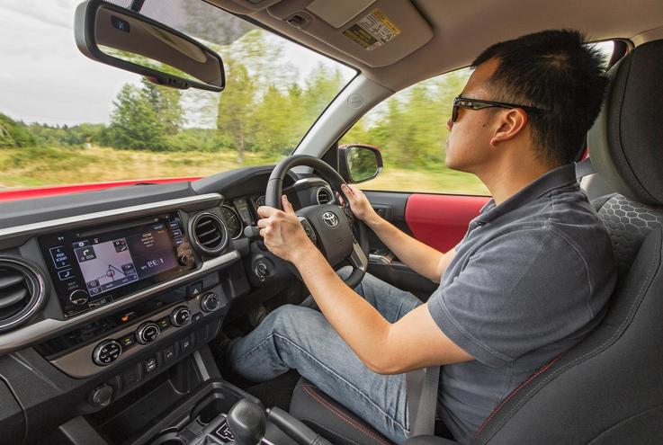 Gambar ini menunjukkan seorang pria duduk di bangku pengemudi mobil dengan tangan memegang kemudi dan memakai kaca mata