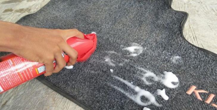 Gambar ini menunjukkan sebuah tangan memegang spray yang berisi foam pengharum dan busa di atas karpet