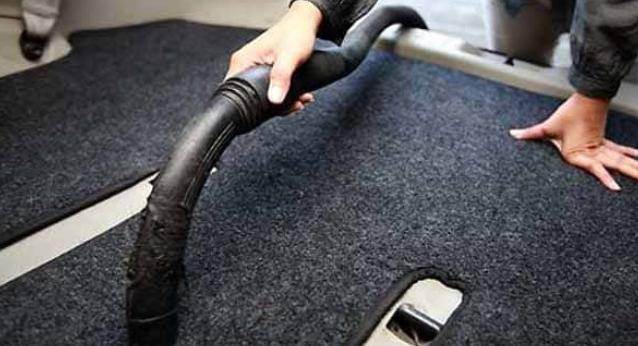 Gambar ini menunjukkan seseorang sedang menyedot debu pada karpet Mobil