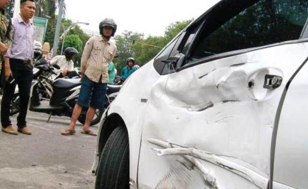 Gambar ini menunjukkan sebuah mobil warna putih penyok ditabrak dari arah samping