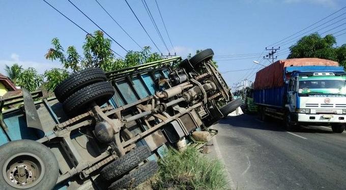 Gambar ini menunjukkan Sebuah mobil terbalik di pinggir jalan