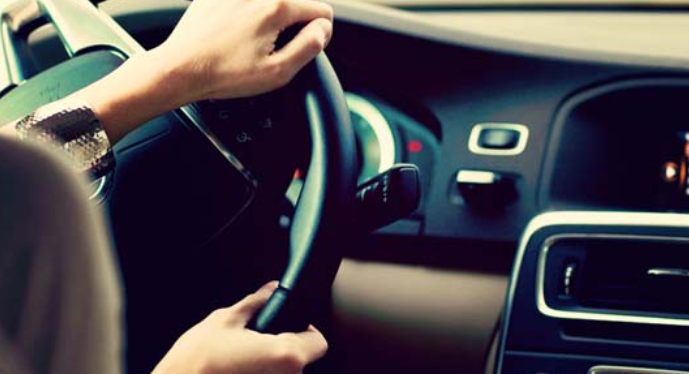 Gambar ini menunjukkan 2 buah tangan sedang memegang kemudi mobil dan mengisyaratkan membelok