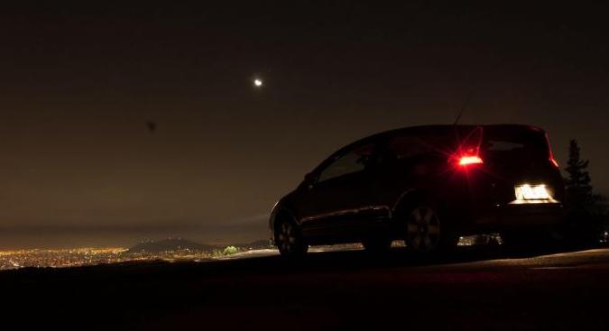 Gambar ini menunjukkan sebuah mobil warna merah sedang berhenti dalam kondisi malam hari