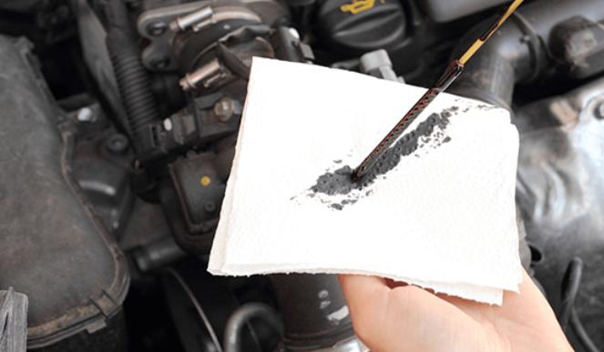 gambar ini menunjukkan tangan memegang alat pengukur oli dan satunya memegang kain