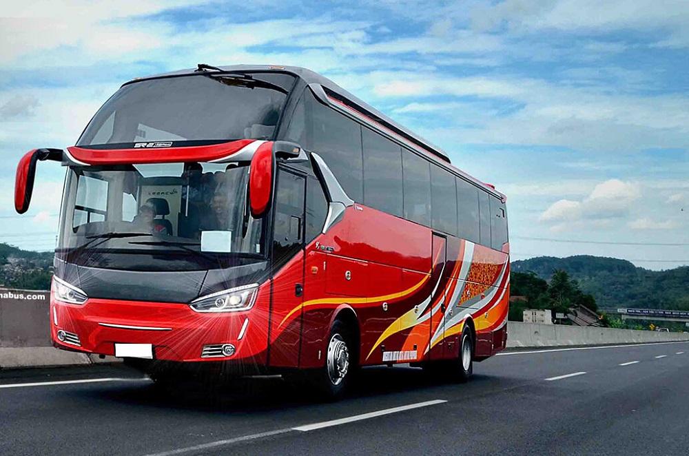 Gambar bus warna merah melaju di jalan raya