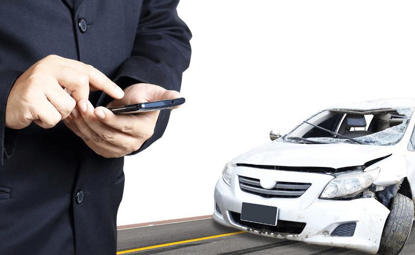 Gambar ini menunjukkan seseorang sedang memegang hp dan terlihat mobil warna putih di belakangnya dalam keadaan rusak