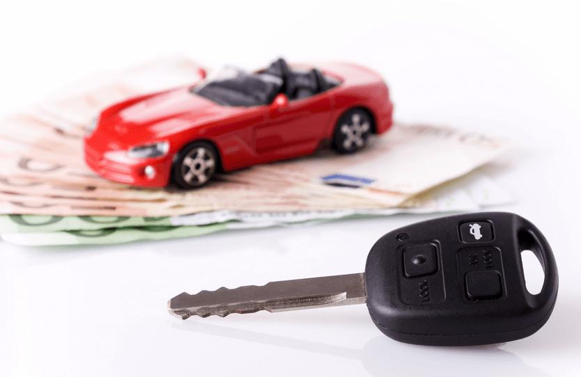 Gambar ini menunjukkan sebuah kunci Mobil dengan terlihat dibelakangnya Mobil merah dan uang keadaan samar