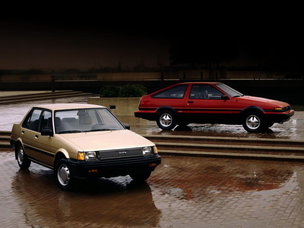 gambar menunjukan dua mobil Toyota Corolla berwarna kuning dan merah sedang diparkir di jalan