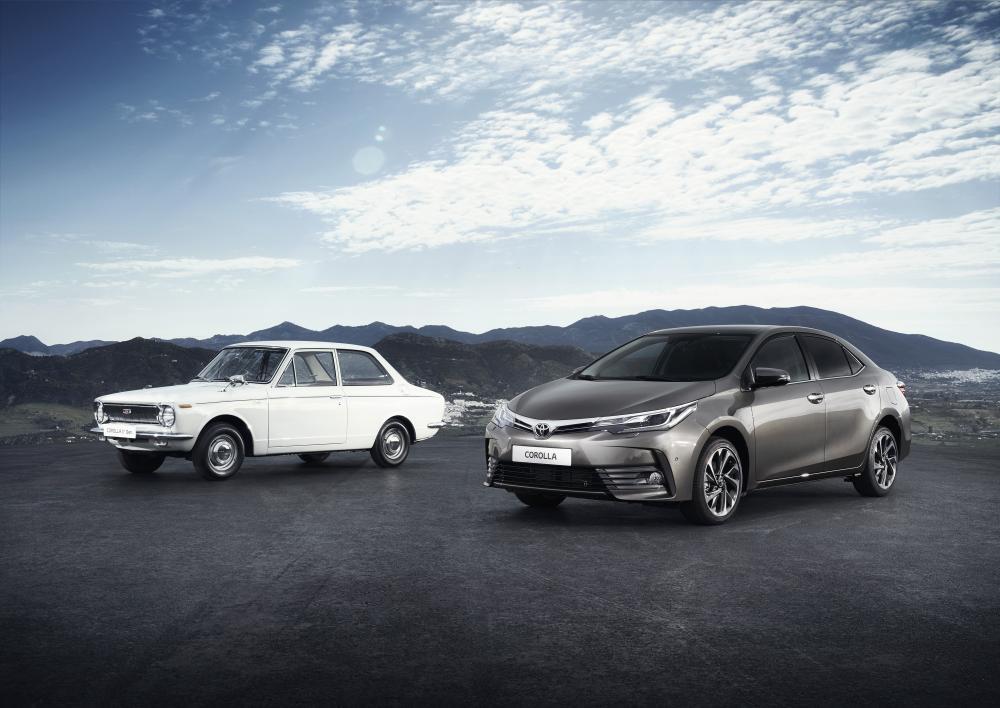 gambar menunjukan dua mobil Toyota Corolla generasi I dengan generasi XI berwarna putih dan abu abu