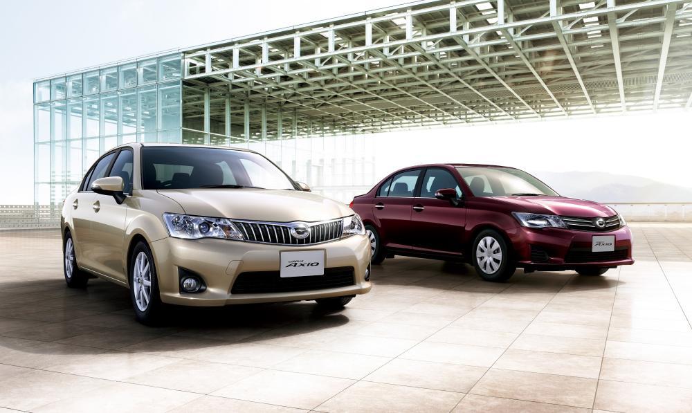gambar menunjukan dua mobil Toyota Corolla Axio berwarna kuning dan merah sedang diparkir di jalan