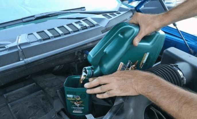 Gambar ini menunjukkan 2 buah tangan memegang derigen yang berisi oli dan mengisikannya pada mesin kendaraan