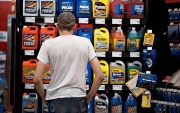 Gambar ini menunjukkan seorang pria sedang berdiri dan di depannya terdapat oli dengan berbagai jenis