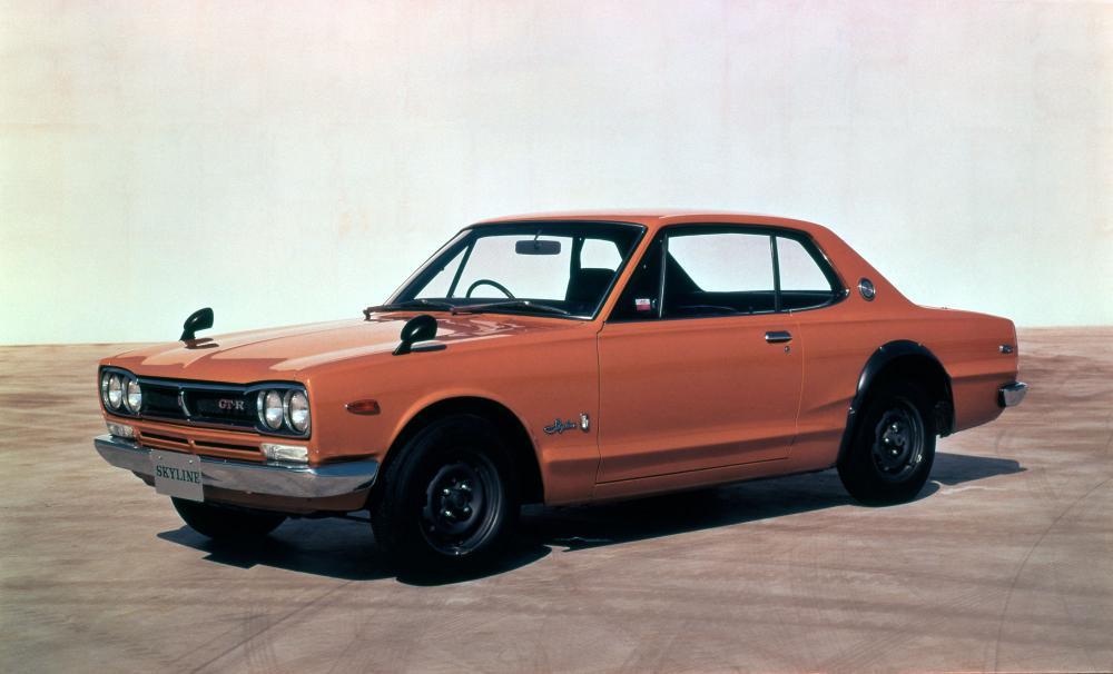 gambar menunjukan sebuah mobil Nissan Skyline GT-R berwarna orange sedang diparkir