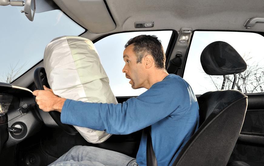 Gambar ini menunjukkan seorang pria sedang mengemudi dan terdapat airbag di depannya sedang mengembang