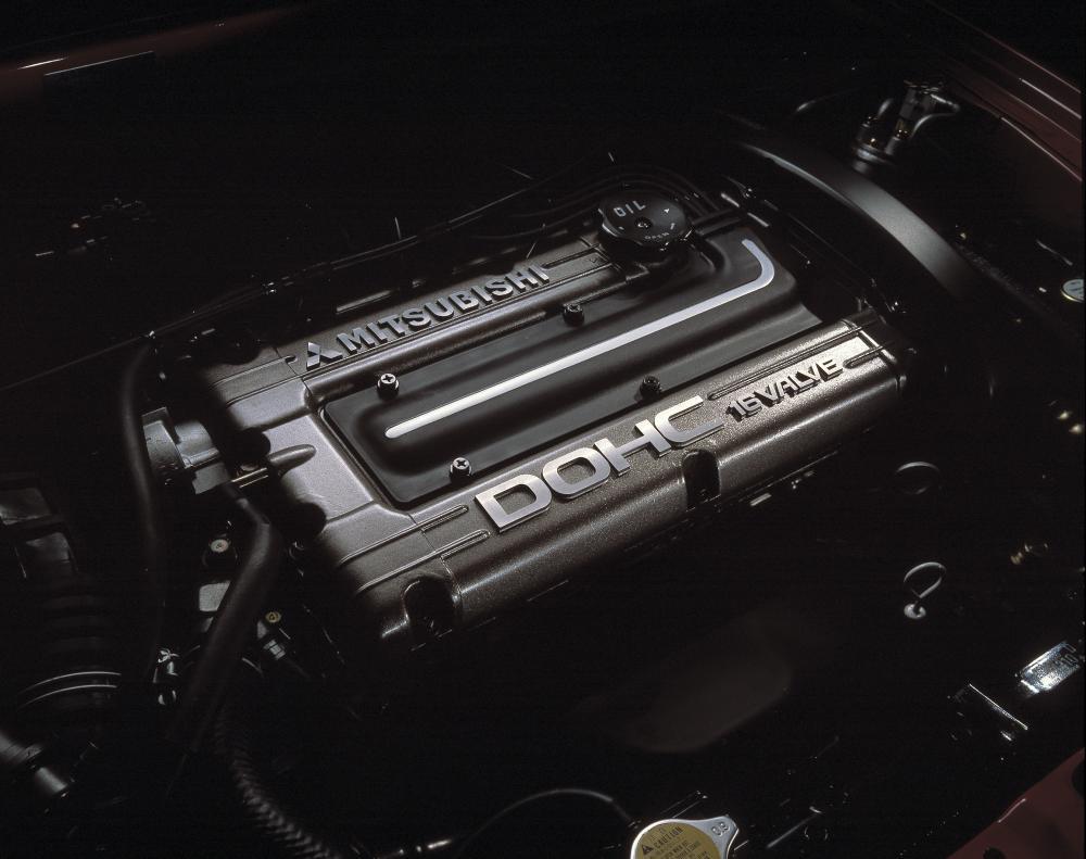 Gambar ini menunjukkan mesin  Mitsubishi 4G63 dengan tulisan Mitsubishi dan warna merah sera hitam di bagian atasnya