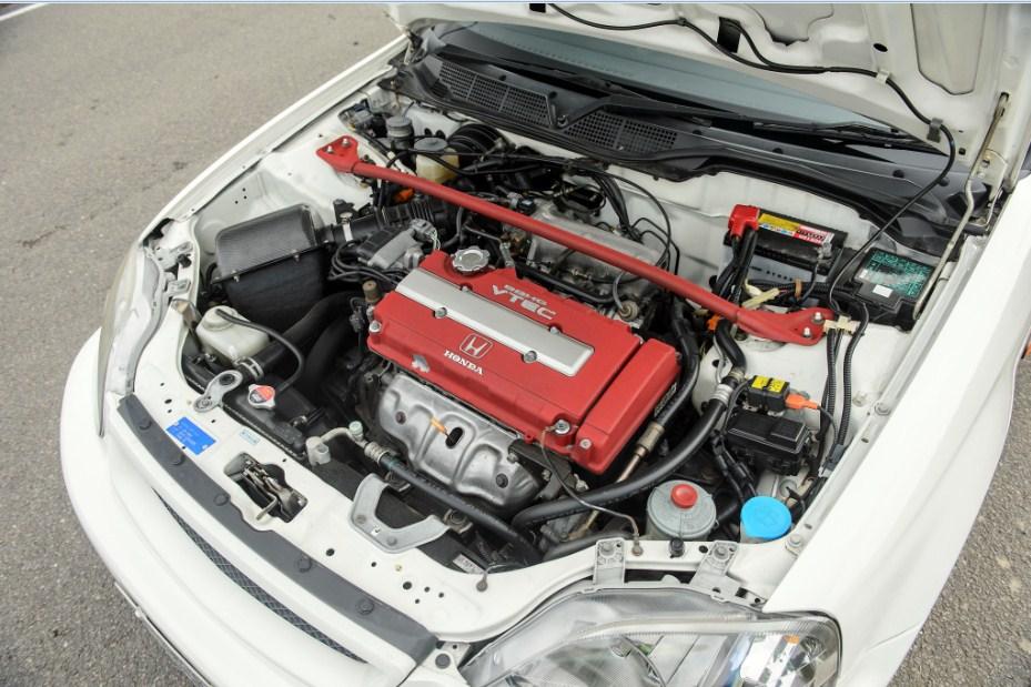 Gambar ini menunjukkan mesin Honda B16B dengan tutup warna merah dan silver yang bertuliskan DOHC VTEC dan HONDA