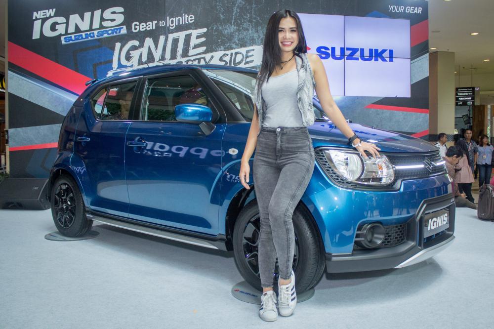 Seorang model berpose di samping Suzuki Ignis Sport Edition