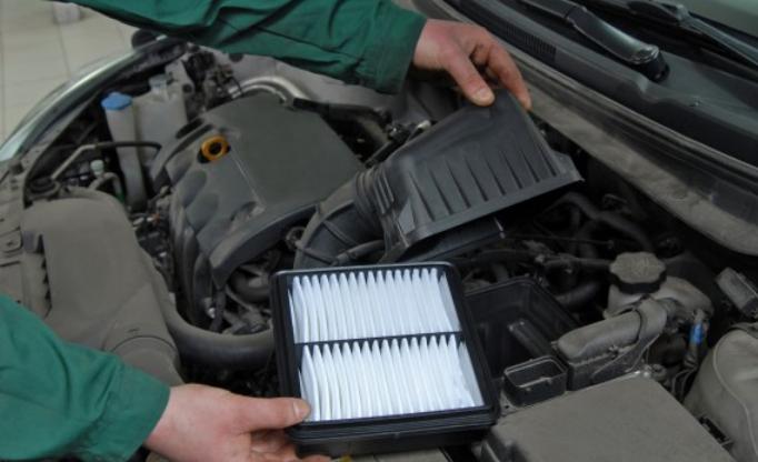 Gambar ini menunjukkan 2 buah tangan sedang memegang filter udara pada mesin Mobil