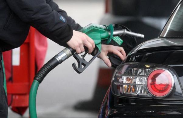 Gambar ini menunjukkan seseorang memegang alat pengisi bahan bakar di dekatkan pada MObil