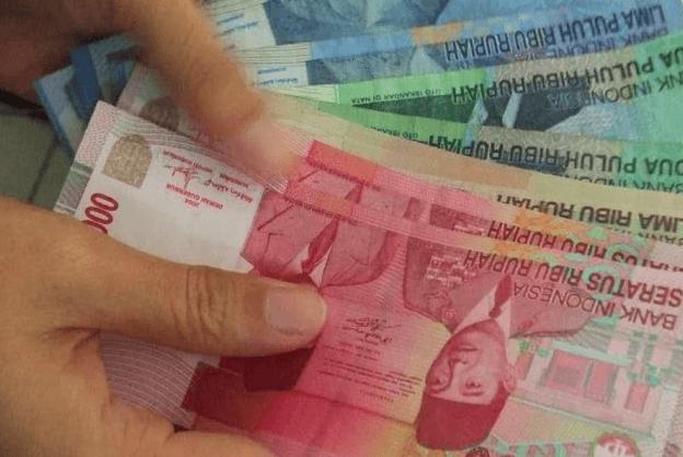 Gambar ini menunjukkan jari tangan memegang uang lembaran 100 ribu, 50 ribu dan 20 ribu