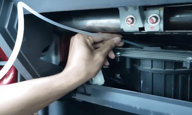 Gambar ini menunjukkan sebuah selang yang dipegang diarahkan menuju blower pada ac mobil