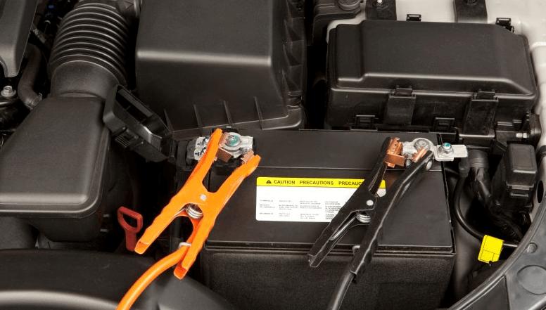 Gambar ini menunjukkan aki Mobil dengan kabel dan penjepit dipasangkan pada terminal aki Mobil