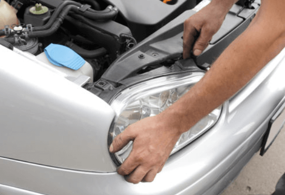 Gambar ini menunjukkan 2 buah tangan sedang memegang lampu utama pada sebuah Mobil warna putih