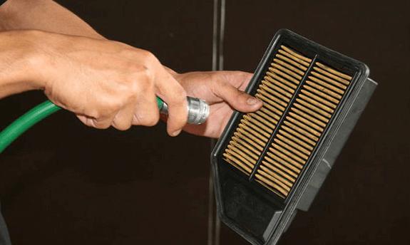 Gambar ini menunjukkan 2 buah tangan sedang memegang filter udara dan selang untuk menyemprotkan angin bertekanan