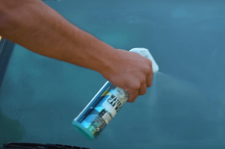 Gambar ini menunjukkan sebuah tangan memegang cairan waterless disemprotkan pada kaca Mobil