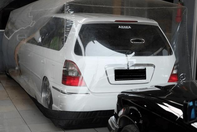 Gambar ini menunjukkan sebuah Mobil warna putih di garasi dengan ditutup bubble cover dan terdapat mobil hitam di belakangnya