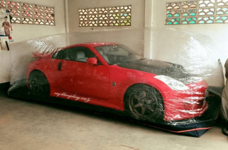 Gambar ini menunjukkan Mobil warna merah yang ditutupi dengan amazon bubble cover dalam sebuah ruangan