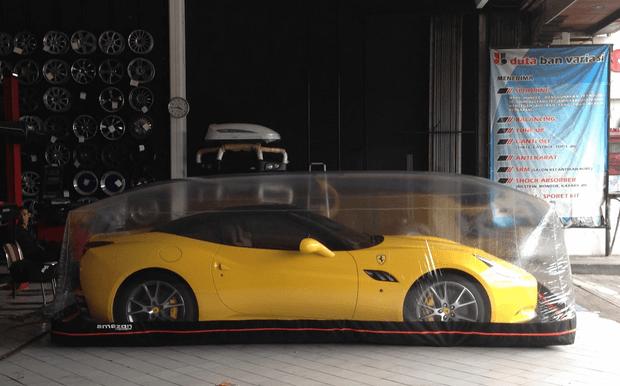 Gambar ini menunjukkan mobil warna kuning tampak samping yang ditutupi dengan cover balon plastik