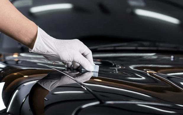 Gambar ini menunjukkan sebuah tangan dengn sarung tangan putih memegang alat diletakkan di atas Bodi Mobil