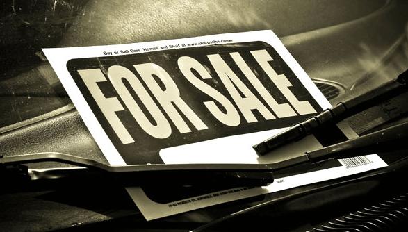 Gambar ini menunjukkan sebuah tulisan for sale di kertas yang terselip pada wiper Mobil