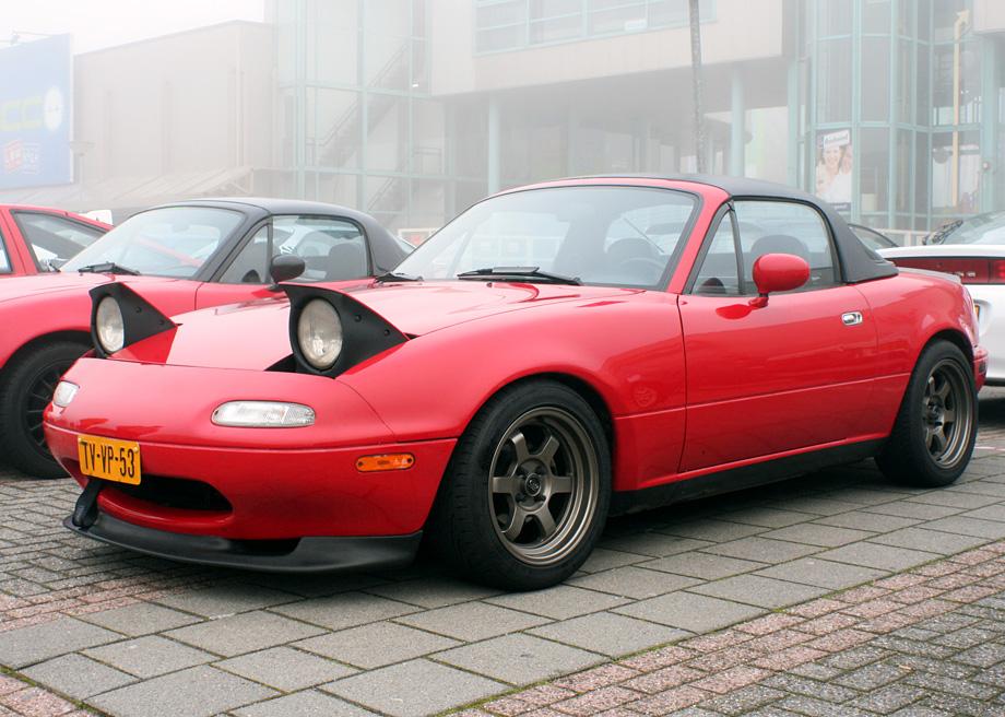Gambar yang menunjukan mobil lama Mazda MX-5 Miata yang memiliki lampu pop up
