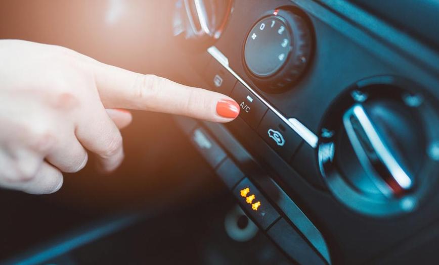Gambar ini menunjukkan sebuah tangan menunjuk tombol ac Mobil pada Dashboard