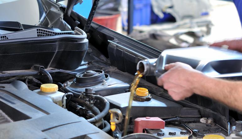Gambar ini menunjukkan sebuah tangan memegang derigen berisi oli sedang dimasukkan ke dalam tangki oli mesin Mobil