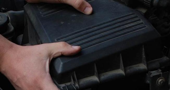 Gambar ini menunjukkan tangan sedang memegang wadah filter Mobil untuk dibuka