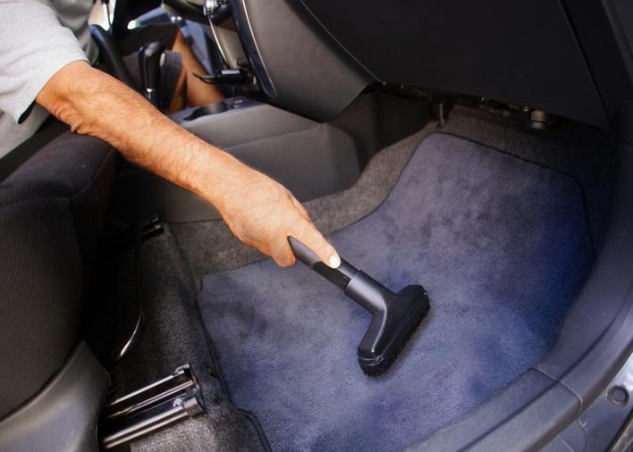 Gambar ini menunjukkan sebuah tangan memegang alat penyedot debu dan membersihkan kabin Mobil