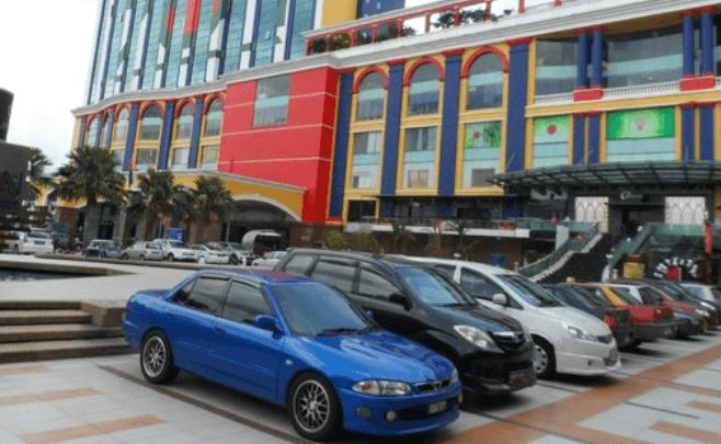 Gambar ini menunjukkan beberapa mobil warna biru, hitam, putih sedang parkir di depan gedung