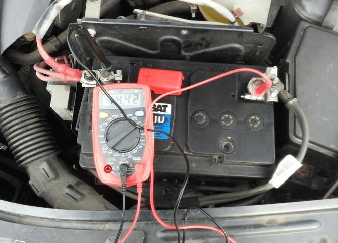 Gambar ini menunjukkan voltmeter sedang dipasangkan pada aki Mobil