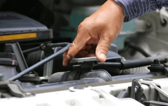 Gambar ini menunjukkan sebuah tangan sedang membuka tutup radiator pada mesin Mobil