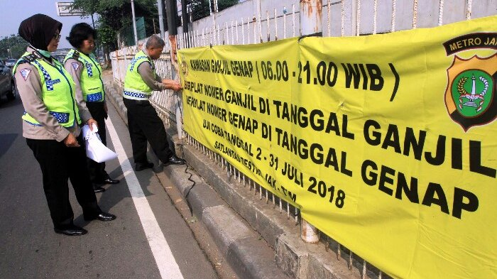 Gambar yang menunjukan petugas kepolisian yang sedang memasang banner peraturan genap ganjil