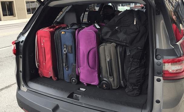Gambar ini menunjukkan beberapa tas koper yang ditata rapi dalam bagasi Mobil