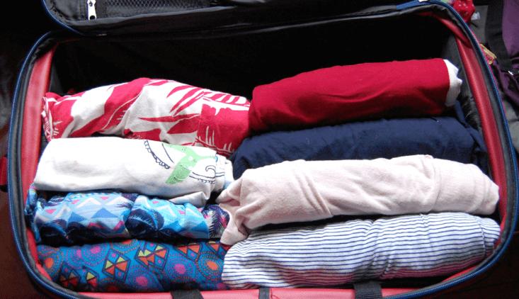 Gambar ini menunjukkan beberapa lipatan baju dengan warna dan motif berbeda ditata dalam tas