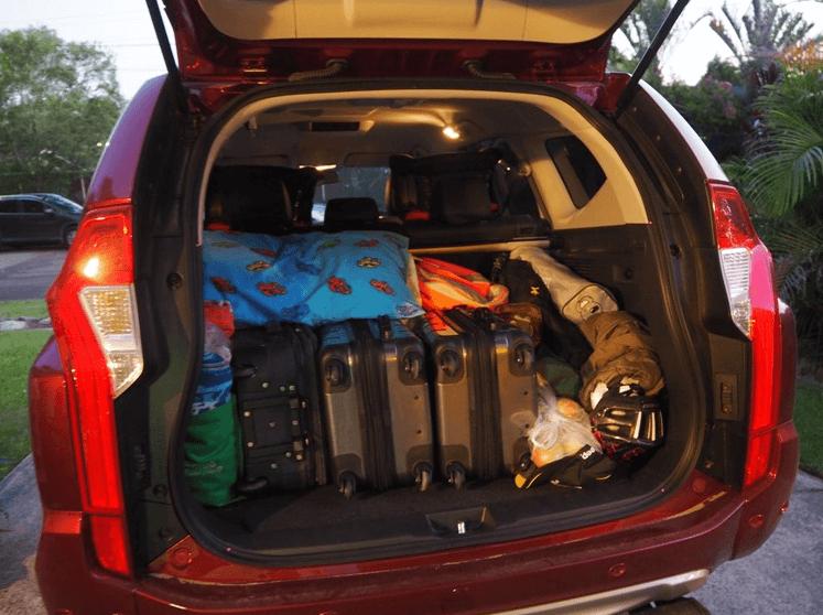 Gambar ini menunjukkan beberaoa koper dan tas di tata dalam bagasi Mobil dengan rapi