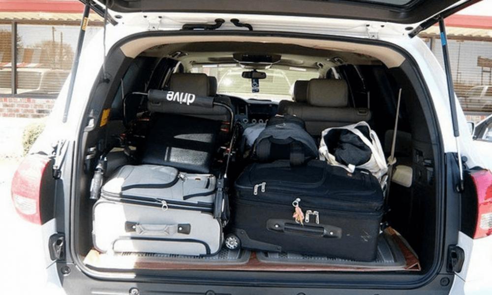Gambar ini menunjukkan 2 buah tas koper warna hitam dan putih ditata berjejer dalam bagasi Mobil