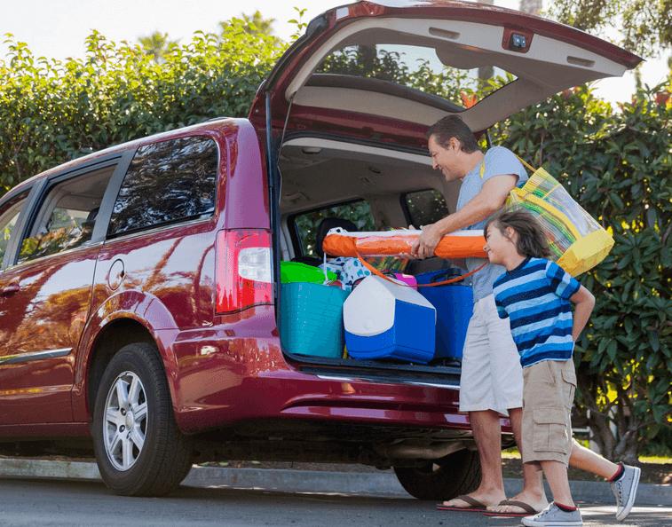 Gambar ini menunjukkan seorang pria dan anak-anak sedang memasukkan barang bawaan ke dalam bagasi Mobil warna merah