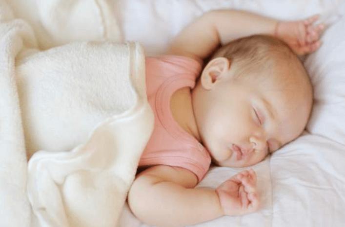 Gambar ini menunjukkan seorang bayi sedang tertidur pulas dan juga diselimuti